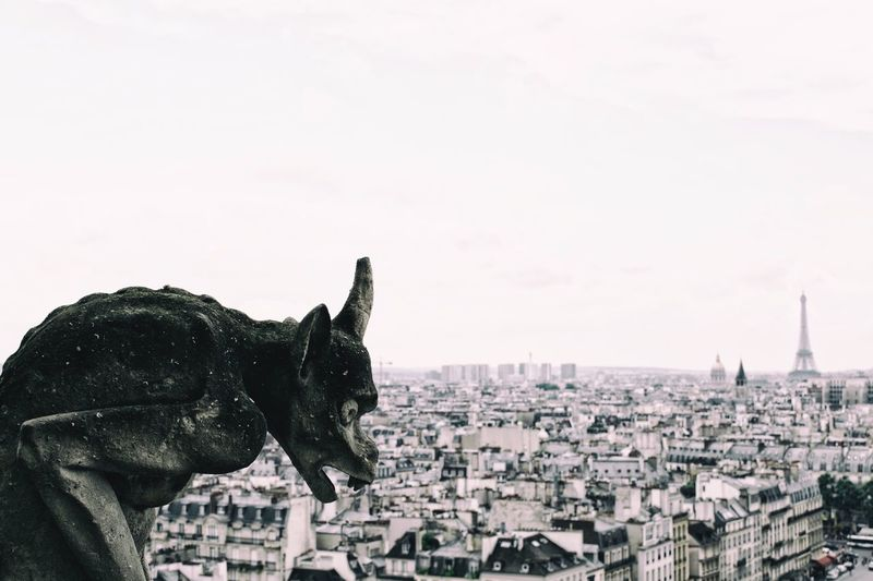 Close-up of gargoyle statue over cityscape against sky