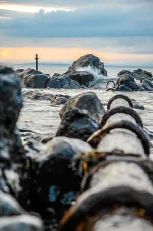 Broken Pipeline Cross Grave Horizon Over Water Metal Metal Cross Nature And Manmade Outdoors Pipe Pipeline Remote Rock - Object Rocks Rocky Rustic Scenics Sea Sea And Sky Selective Focus Sunset Surface Level Tranquil Scene Tranquility Water Waves And Rocks
