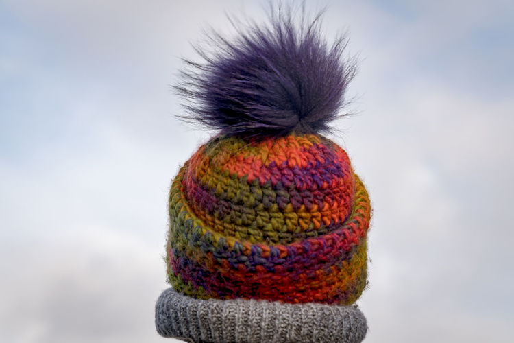 Close-Up Of Woman Wearing Knit Hat Against Cloudy Sky