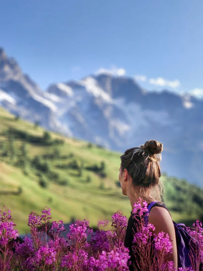 Rear view of woman on purple flowering plants against sky