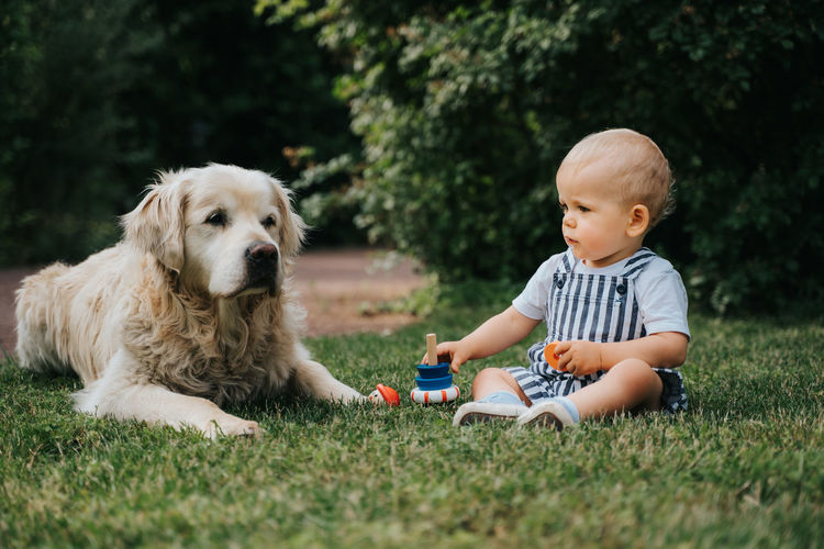 Cute toddler with dog sitting on lawn