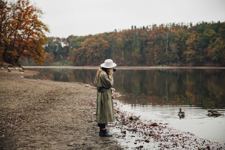 Side view of woman wearing hat photographing birds while standing by lake against sky