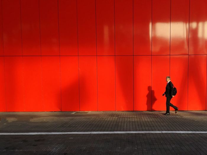 Full length of man walking on sidewalk against red wall