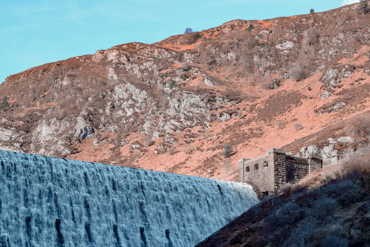 Human made giant waterfall Waterfall Dam Elan Valley, Wales Morning Morning Light Flowing Water Falling Water Wales UK Victorian Victorian Engineering Wintertime Coral Colored Turquoise Colored Light And Shadow Power Generation Water Supply Clean Water Flowing Mountain Blue Sky Landscape Rugged Rough Force Rocky Mountains Geology Physical Geography Rock Formation Rock