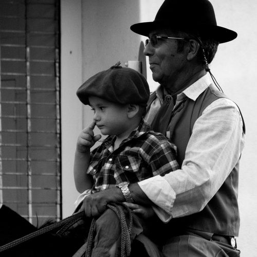Father and son riding horse in city