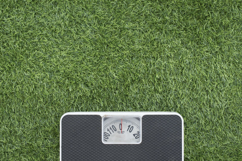 photo of a weighing scale on a green grass (lose weight concept) Grass Green Weighing Scale Close-up Conceptual Conceptual Photography  Day Fat Fitness Flat Lay Green Color Healthy Lifestyle High Angle View Lose Weight No People Numbers Outdoors Shoes Sports