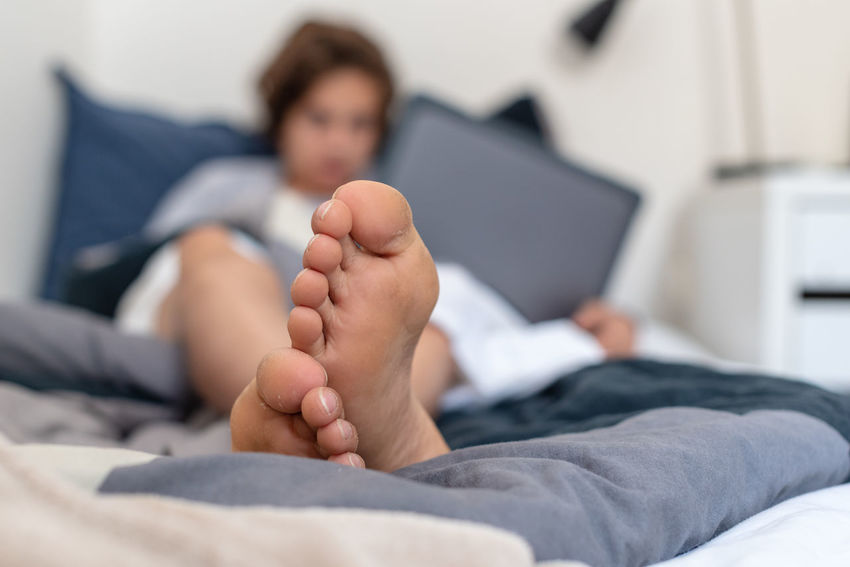 Teenage boy's feet barefoot Bed Child Childhood Comfortable Domestic Life Domestic Room Focus On Foreground Front View Furniture Home Interior Human Foot Indoors  Lifestyles Lying Down Real People Relaxation Resting This Is My Skin
