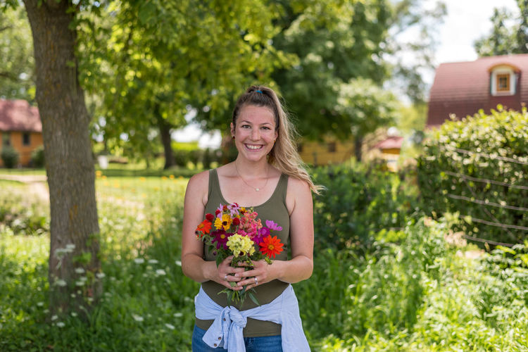 Portrait of smiling young woman holding flowering plants