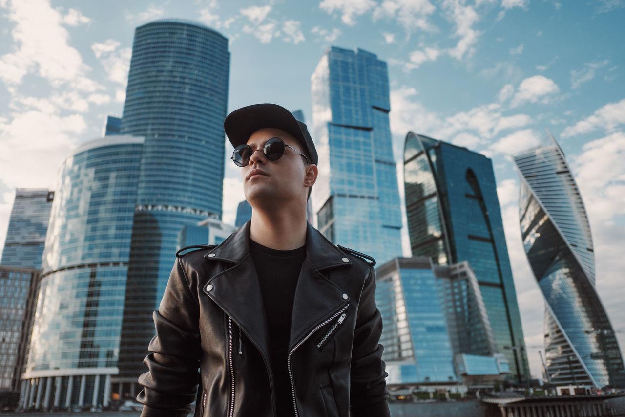 Man standing by modern buildings in city