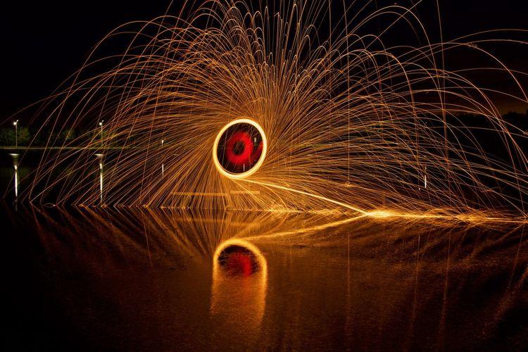 Illuminating light painting at night by lake