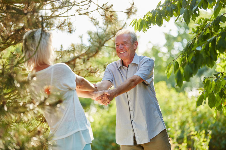 Couple Holding Hands While Standing Amidst Trees