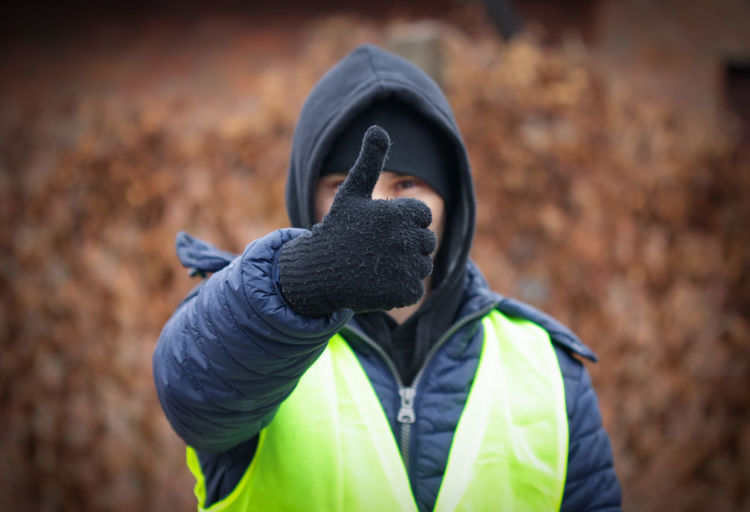 Portrait of man wearing warm clothing while gesturing thumbs up