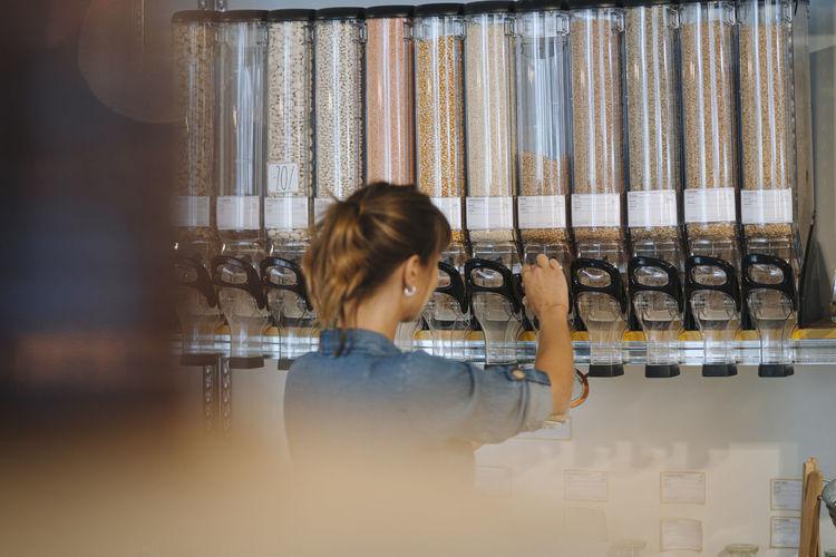Rear view of woman working in shelf