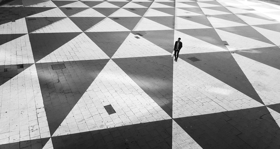 High angle view of person walking on tiled floor