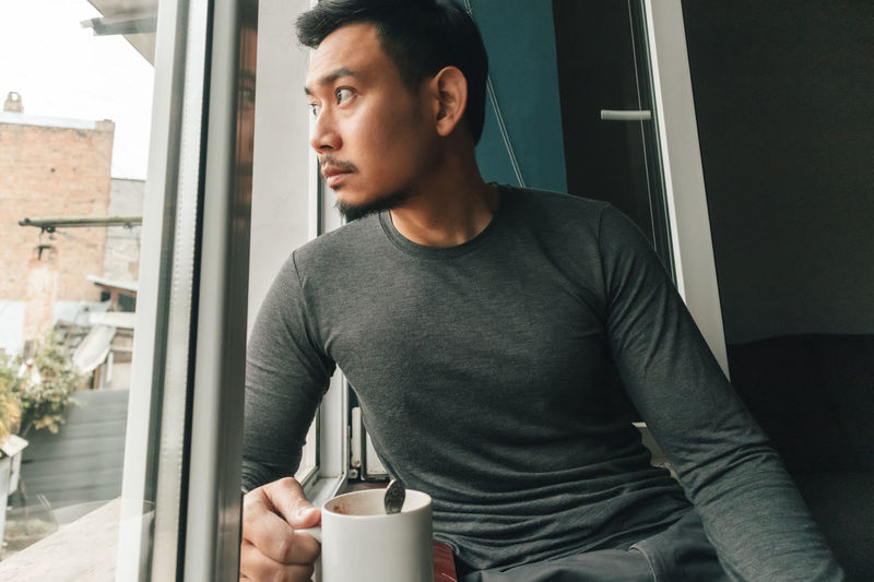 Man looking away while standing on window at home