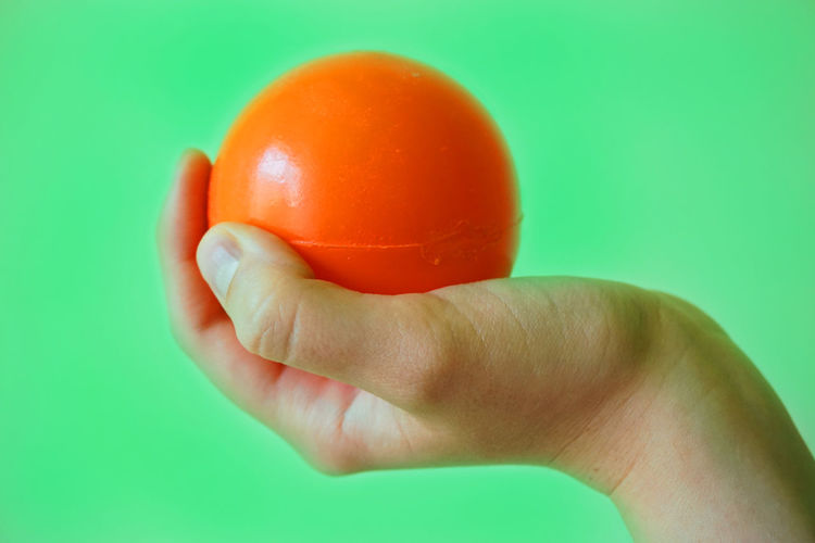 Ball Close-up Day Holding Human Body Part Human Hand Indoors  Juggling One Person Orange Color People Plastic Real People Studio Shot