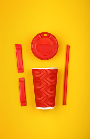 Flat lay of coffee-to-go, disposable red paper cup, drinking straw and sugas sticks over yellow background Vibrant Color Directly Above Still Life Close-up High Angle View Copy Space Yellow Studio Shot Red Colored Background No People Yellow Background Group Of Objects Food And Drink Coffee Tea Coffee To Go Take Away Paper Cup Coffee Cup Drinking Straw Sugar Modern Flat Lay Hot Drink