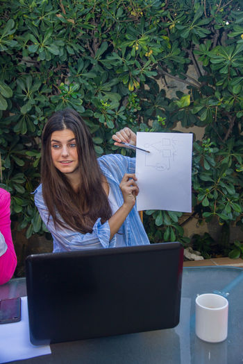 Young enterprising woman shows to the other co-workers an outline on a white paper. Company Females Show Teamwork Work Working Young Business People Corporate Coworkers Diagram Employees Explaining  Girls Job Laptop Outline Paper People Professional Project Scheme Successful Teach Women