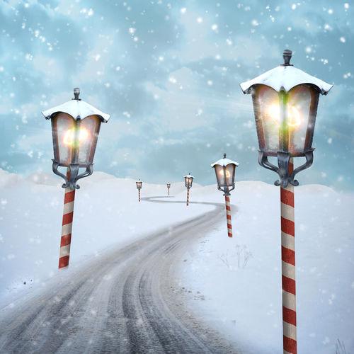Digital composite image of illuminated street lights at roadside during snowfall