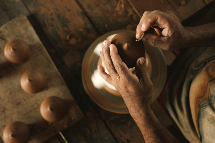 Cropped hands of man making pottery at workshop