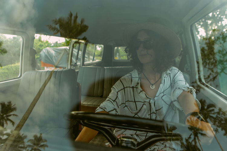 A young woman wearing a wide brim hat and sunglasses poses inside a Kombi. Clouds Reflected On Glass Drive Driving Film Look Film Photography Front View Girl Glass Reflection Glass Reflections Hat Kombi Kombi Love Land Vehicle Lifestyles One Person Palm Tree Reflection Sitting Summer Summer Style Sunglasses Van Windshield Young Adult Young Woman The Traveler - 2018 EyeEm Awards