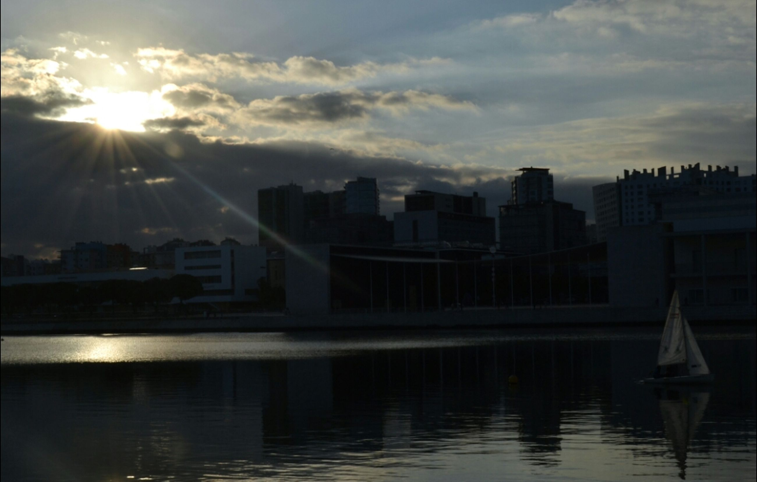 architecture, building exterior, water, built structure, sun, sunbeam, sky, city, reflection, sunlight, waterfront, lens flare, river, sunset, cloud - sky, skyscraper, cloud, cityscape, outdoors, no people