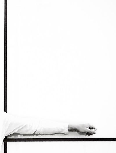 Low section of person on bed against white background