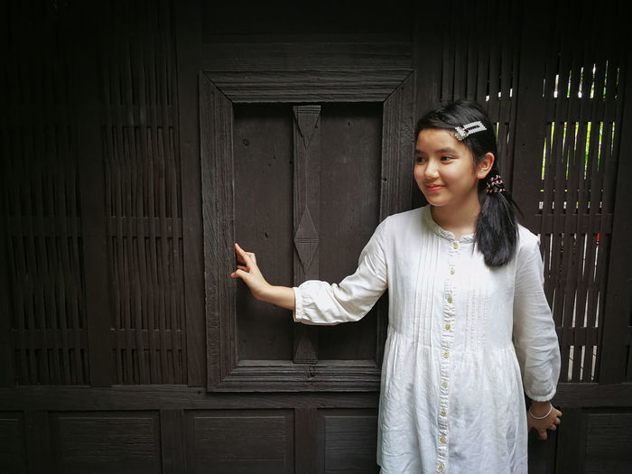 Smiling girl standing against wooden wall