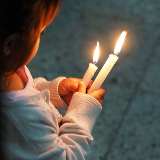 High angle view of girl holding illuminated candles on footpath