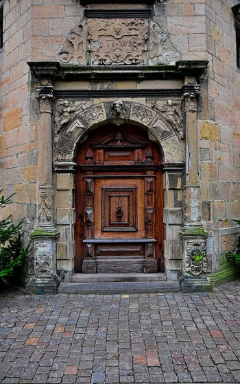 wooden door to the castle Arch Architecture Brick Building Building Exterior Built Structure City Closed Cobblestone Day Door Entrance History No People Old Outdoors Paving Stone Protection Safety Security Stone Stone Wall The Past Wall
