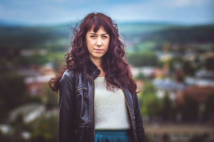Portrait of smiling woman with curly hair standing against townscape