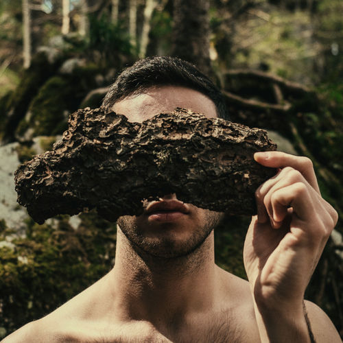 Close-Up Of Shirtless Man Covering Face With Plant Bark
