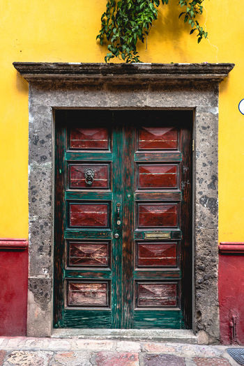 Pattern, Texture, Shape And Form Pattern Abstract Abstract Photography Door San Miguel De Allende Mexico Colorful Colors Geometric Shapes Streetphotography Street Photography Magic Moments Built Structure Architecture Building Exterior No People Day Outdoors Entrance Building House Closed Wood - Material Safety Yellow Security Protection Red Front Door Plant Residential District