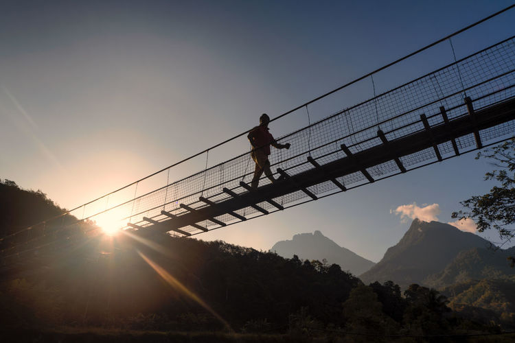 Silhouette man walking on bridge against sky during sunset