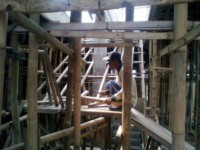 Bamboo, Manpower & Construction One Person Real People Full Length Architecture Day Built Structure Wood - Material Lifestyles Indoors  Casual Clothing Men Young Adult Industry Adult Young Men Working Ladder