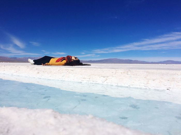 Young woman lying on salt flat against blue sky