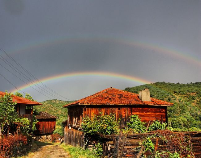 Scenic view of rainbow over houses against sky