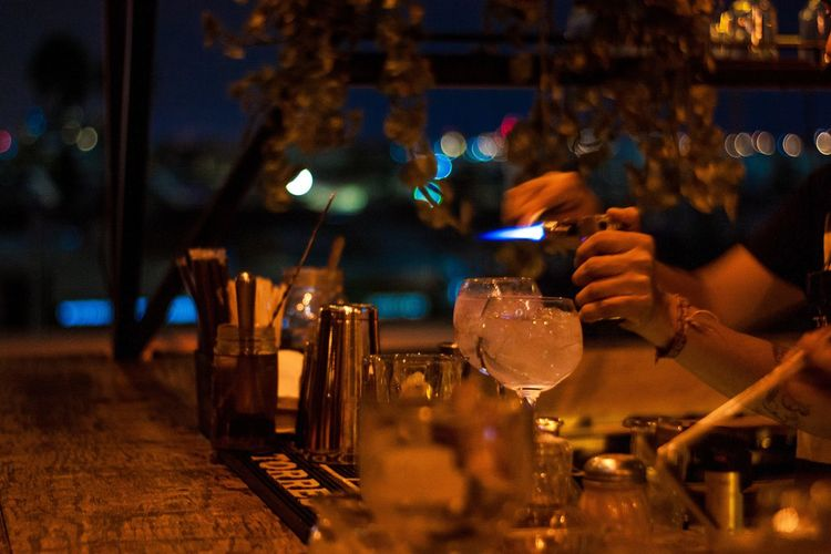 Cropped hands of bartender with drinks on holding lighter in restaurant at night