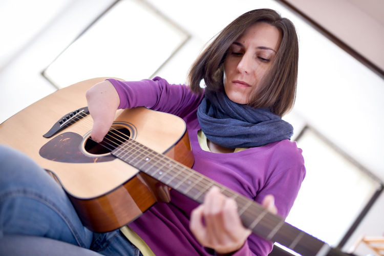 Woman playing guitar at home