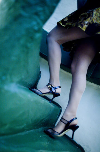Low section of young woman wearing high heels climbing on steps