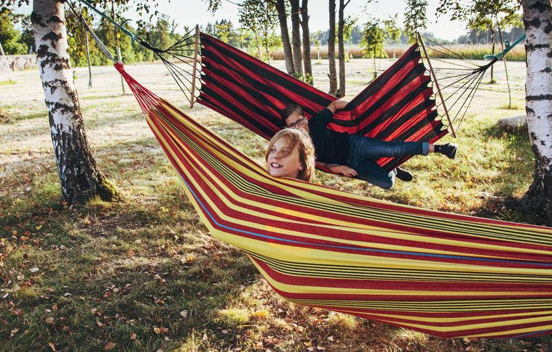 Rear view of boy relaxing on hammock