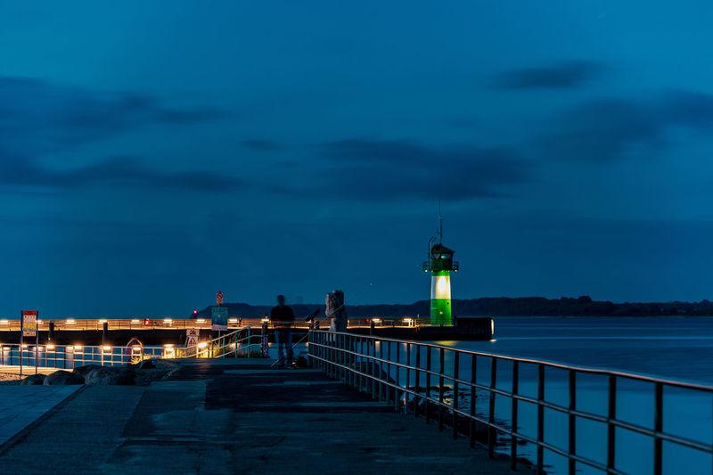 Illuminated lighthouse by sea against sky at dusk