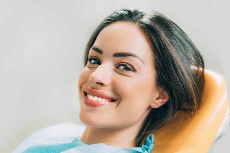 Close-up portrait of smiling patient sitting on chair in dentist office