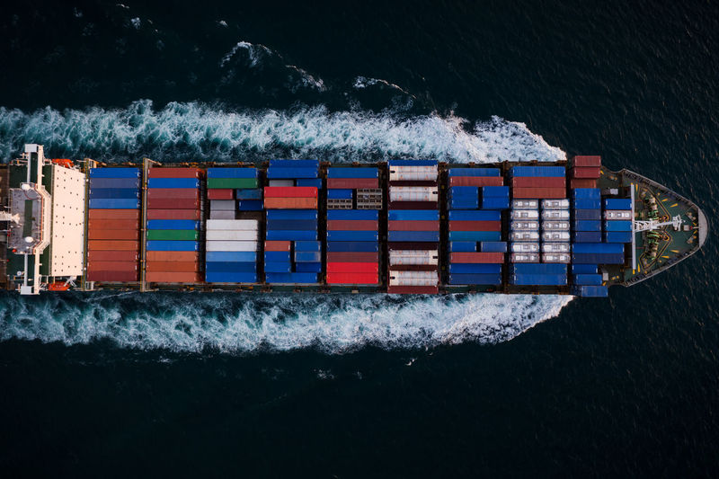 Container ship sailing fast in sea top view at night process, service and international transport
