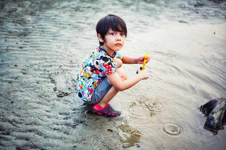 High angle view of boy playing with toy on beach