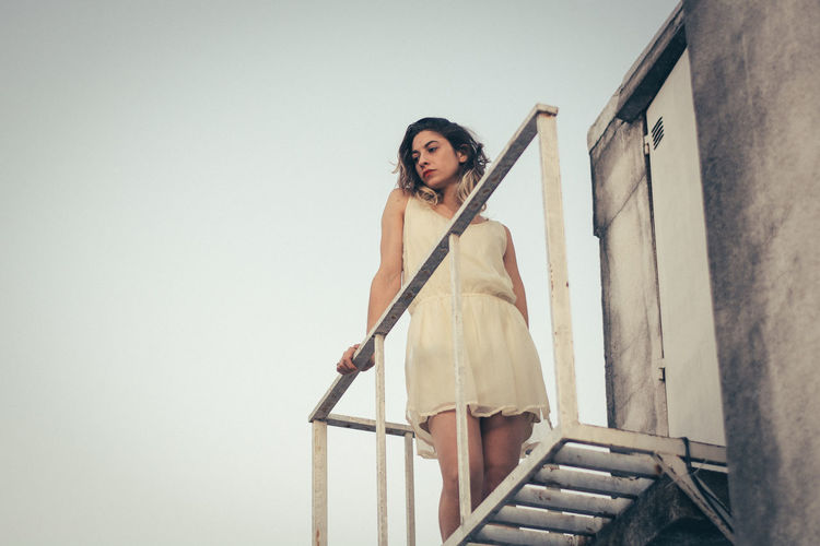 Low angle view of thoughtful young woman looking away while standing on building terrace during sunset