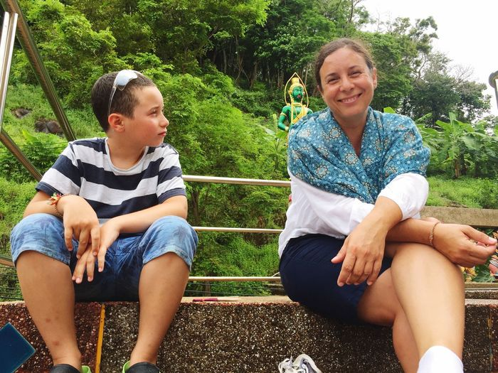 Portrait of smiling mother sitting by son in park