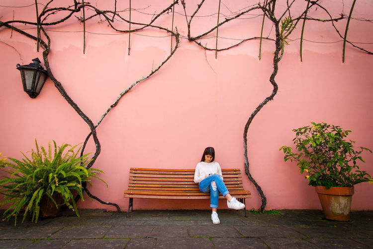 Young woman sitting on bench by wall
