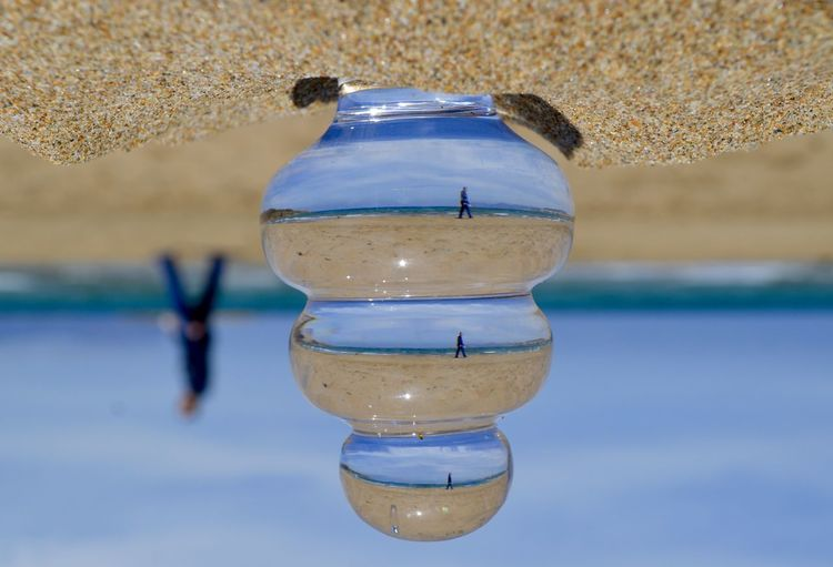 Upside down image of glass at sandy beach