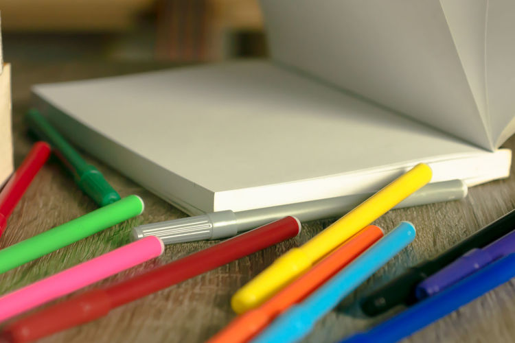 Close-up of colorful felt tip pens with book on table